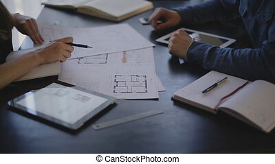 Architect woman and her client is a man sitting at the table and discuss the blueprint