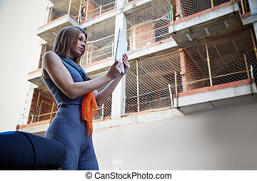 Architect woman real estate checking plan