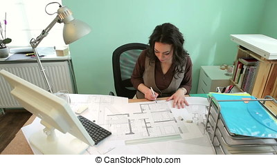 Architect woman working with blueprints at her desk