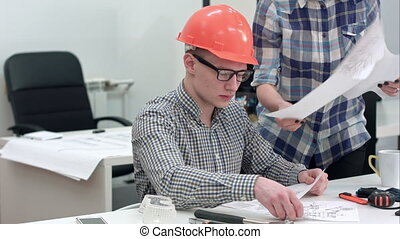 Architect working on blueprints while female colleague bringing more drawings