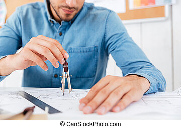 Architect working on construction blueprint in office with divider