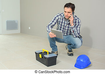 architect working on construction site talking on the phone