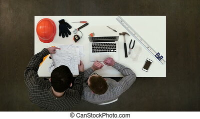 Architect working on laptop while his colleague bringing more drawings