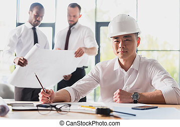 architect working on new project with colleagues behind in modern office