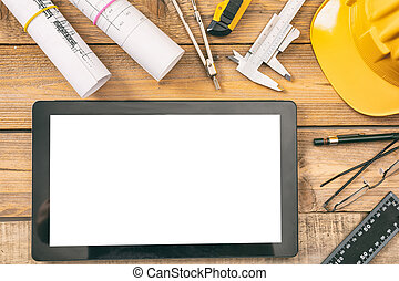 Architect workplace. Tablet with white blank screen, project construction blueprints and engineering tools on wooden desk, copy space, top view