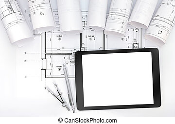 architect workspace with blueprint rolls, tablet and drawing instruments