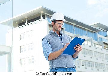 Architect writing on clipboard - Male architect writing on ...