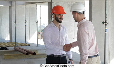 Architector and builder shake hands at the building under construction