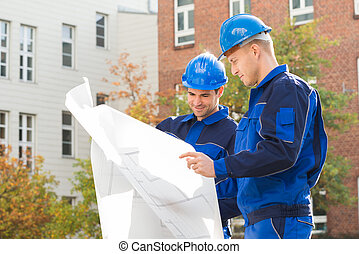 Architects Analyzing Blueprint Together