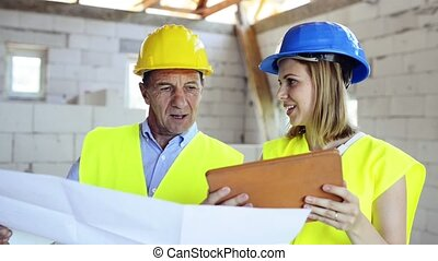 Architects or civil engineers with tablet looking at plans of a new house, discussing issues at the construction site.