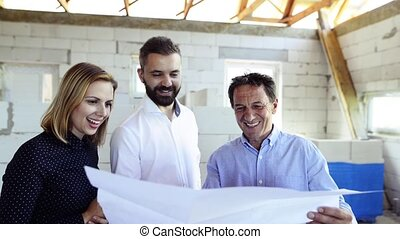 Young couple with architect or civil engineer looking at plans of their new house, discussing issues at the construction site.