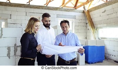 Architects and civil engineer at the construction site. -...