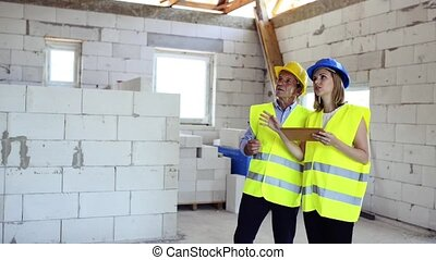 Architects and home owner with tablet at the construction site.