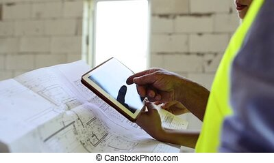 Architects and home owner with tablet at the construction...