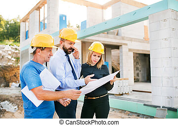 Architects and worker at the construction site. - Architect...