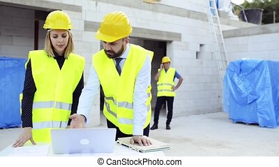 Architects and worker at the construction site.