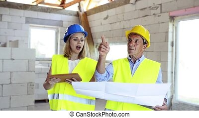 Architects and worker with tablet at the construction site.