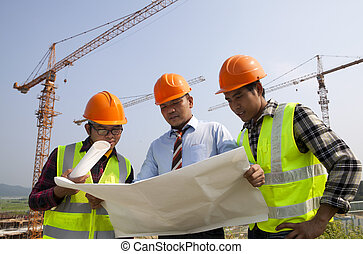 Architects at a construction site looking at blueprint...