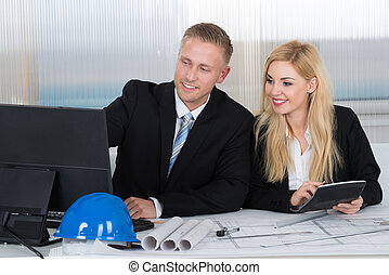 Architects Discussing Over Computer In Office