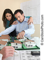 Architects gathered around model replica of housing estate