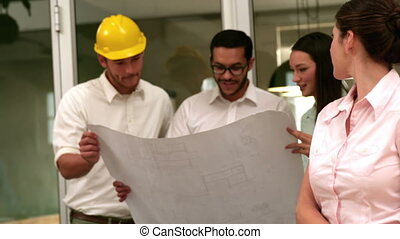 Architects going over blueprints - Team of architects going...