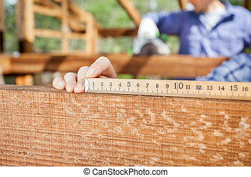 Architect's Hand Measuring Wood At Site