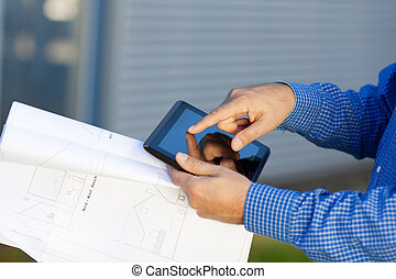 Architect's Hands Holding Blueprint While Using Digital Tablet
