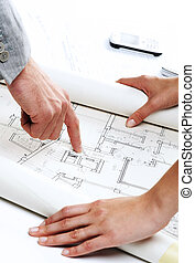 Architect?s hands pointing on the blueprint of new house project