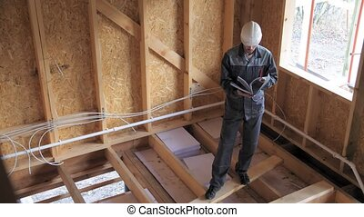 Architects or builder check plans in a half built timber frame house. Builder on a construction site with a documents. 4k