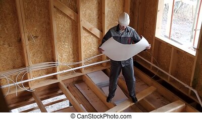 Architects or builder check plans in a half built timber frame house. Builder on a construction site with a plan. 4k