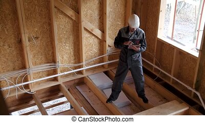 Architects or builder check plans in a half built timber frame house. Smiling Builder on a construction site with a tablet. 4k