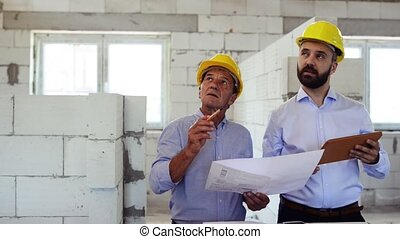 Architects or civil engineers with tablet at the construction site.