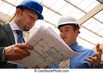 Architects Reviewing Blueprint - Two architects reviewing ...