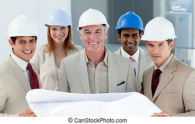 Architects with hardhats in a building site smiling at the...