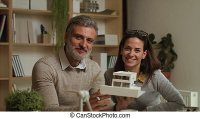 Architects with model of house indoors in office, looking at camera.