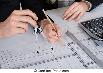 Architects Working On Blueprint At Desk In Office
