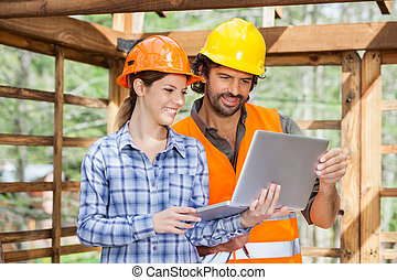 Architects Working On Laptop At Construction Site - Male and...