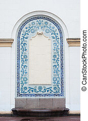 architectural arch on facade of building with blue stucco