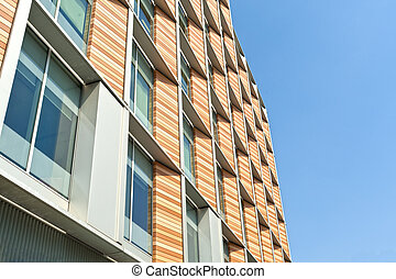 architectural detail of a tall building with glass wood and steel