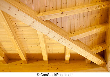 Interior architectural details of a wooden ceiling showing beams and joins extending into a corner
