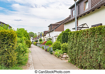 Architectural duplex houses with hedges and flowers in Germany