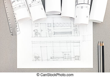architectural hand-drawn sketch with blueprint rolls on desktop