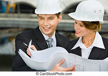 Architectural plan - Confident female worker is showing a...