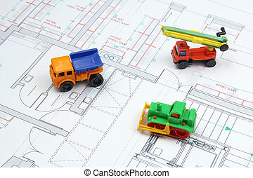 architectural plans and toy bulldozer, dump truck