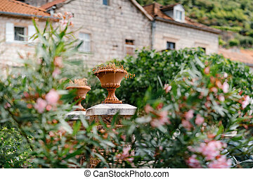 Architectural pot on stone columns in the garden against the background of the house.
