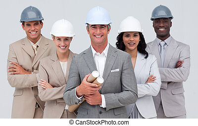 Architectural team smiling at the camera with hard hats and...