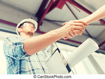 builder with blueprint shaking partner hand