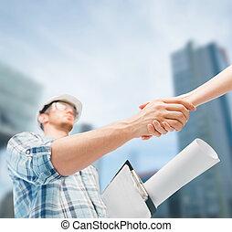 builder with blueprint shaking partner hand