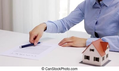 woman with house model and pen signing contract