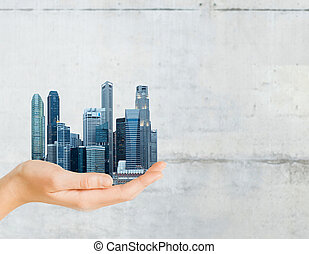 hand holding city over gray concrete background